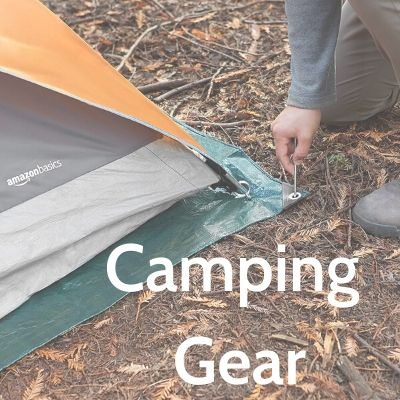 staking a tent at a wooded campsite